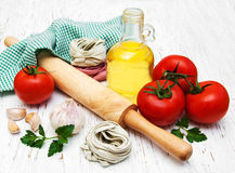 Olive oil,  fettuccine nest, garlic and tomatoes Royalty Free Stock Image