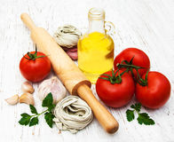 Olive oil,  fettuccine nest, garlic and tomatoes Royalty Free Stock Photos
