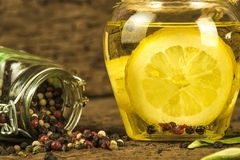 Olive oil flavored with lemon and  peppercorns. In  glass bottle on old wooden background Royalty Free Stock Images