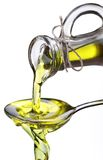 Olive oil flowing from carafe into the spoon. Olive oil flowing from carafe into the spoon isolated on a white Stock Photos