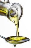 Olive oil flowing from carafe into the spoon. Olive oil flowing from carafe into the spoon isolated on a white Stock Photo