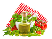 Olive oil with fresh basil leaves and tomatoes isolated on white Stock Photography