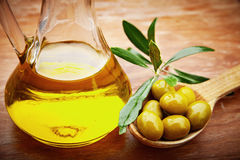 Olive oil with fresh olives on rustic wood Royalty Free Stock Photography