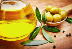 Olive oil with fresh olives on rustic wood Royalty Free Stock Images