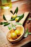 Olive oil with fresh olives on rustic wood Stock Photos