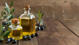 Olive oil and fresh olives on wood background Stock Photography