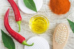 Olive oil, fresh red chili peppers and dry chili powder for preparing diy hair mask against hair loss. stock photo