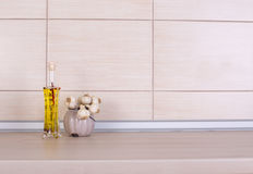 Olive oil and garlic on countertop. Olive oil in glass bottle and garlic in pot on kitchen countertop stock photos