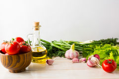 Olive oil, garlic and tomato on the white wooden background Stock Image