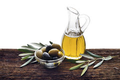 Olive oil. Glass bottle of premium virgin olive oil and some olives with leaves on wooden background royalty free stock photography