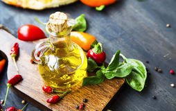 Olive oil glass bottle with spices and basil herb Stock Image