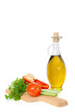Olive oil in a glass jar and fresh vegetables Royalty Free Stock Image