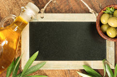 Olive oil and green olives on blackboard Royalty Free Stock Image