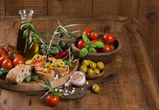 Olive oil with green olives and bread on a wooden surface Stock Image