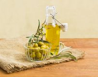Olive oil, green olives and olive branches. Glass bottle of the olive oil with open lid, green olives in small glass bowl and olive branches on a sackcloth on an Royalty Free Stock Photography