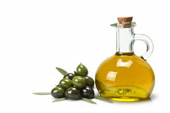 Olive oil for a healthy diet. Glass bottle of premium virgin olive oil and some olives with leaves on a white background royalty free stock photo