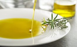 Olive oil pouring with spices and herbs to plate close up stock images