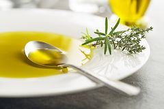 Olive Oil with herbs. Healthy olive oil with herbs pouring with spoon close up stock photos