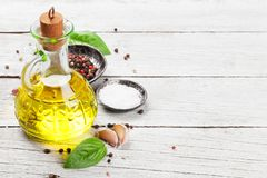 Olive oil, herbs and spices. Olive oil, pepper and salt. Spices on wooden table. Cooking concept. With space for your text Royalty Free Stock Images