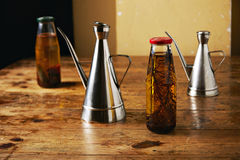Olive oil with herbs and steel dispensers. Rough rustic wooden table with two bottles of flavored olive oil and two stainless steel cruets against beige wall Royalty Free Stock Photos