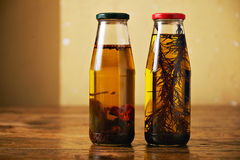 Olive oil with herbs on a wooden table. Two glass bottles with metal caps with olive oils with herbs and chilli peppers on a vintage brown table against beige Stock Photos