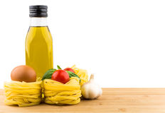 Olive oil, Italian noodles, tomatoes, garlic and basil on board Royalty Free Stock Image