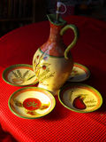 Olive oil jug with a set of 4 plates. Ceramic Olive oil jug accompanied by four small plates, glazed and nicely decorated with hand painting Royalty Free Stock Images