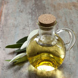 Olive Oil and Olive Leaves on Rustic Timber Stock Photos