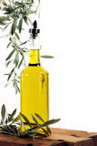 Olive Oil with Olive Tree Branches. A glass bottle of extra virgin olive oil on wood surface surrounded with leafy olive tree branches, white background royalty free stock photography