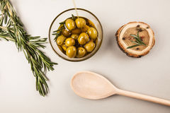 Olive oil and olives in bowl. Olives and olive oil in glass bowl with rosemary, spices and wood, isolated on white Royalty Free Stock Photography