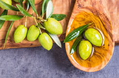 Olive oil and olives. Extra virgin olive oil spoon and olives on dark stone background.Testing fresh mediterranean olive oil Stock Photos