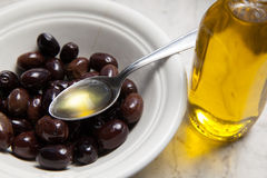 Olive oil and olives on marble. Olive oil and olives on white marble stock photo