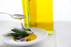 Olive oil and olives on the table. Olive oil and olives on white table stock image