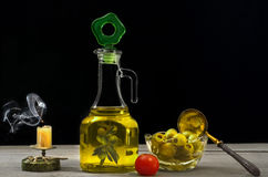 Olive oil, olives and tomatoes on wooden surface and black background. Stock Images