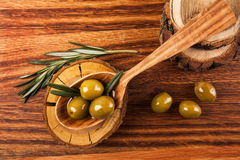 Olive oil and olives. In wooden spoon with rosemary, lying on the wooden table Stock Images