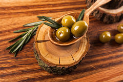 Olive oil and olives. In wooden spoon with rosemary, lying on the wooden table Stock Photography