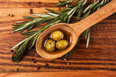 Olive oil and olives. In wooden spoon with rosemary and spices, lying on the wooden table Royalty Free Stock Image