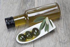 Olive oil and olives on a wooden surface stock photos