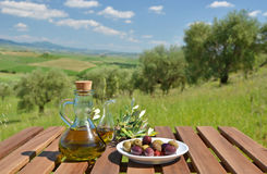 Olive oil and olives and on the wooden table Royalty Free Stock Photo
