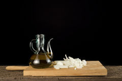 Olive oil and onion  black background. Olive oil and onion  on a old wooden shelf isolated on black  background Stock Photo