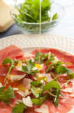 Olive oil over Carpaccio. With arugula and parmesan cheese stock image