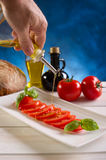 Olive oil over Slice tomato royalty free stock photography