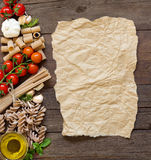 Olive oil, pasta, garlic and tomatoes  with craft paper Stock Image