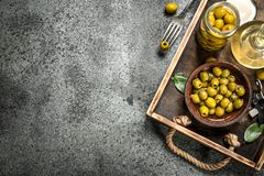 Olive oil with pickled olives on an old tray. On a rustic background Royalty Free Stock Photography