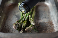 Olive Oil Poured on Asparagus in Baking Tray Royalty Free Stock Images