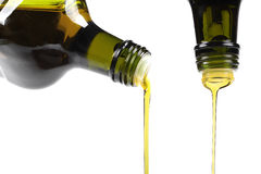 Olive oil pouring from glass bottle Stock Photos