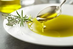 Olive oil pouring to spoon close up. Healthy olive oil with herbs pouring with spoon close up royalty free stock photos