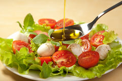 Olive Oil Pouring Over Salad Stock Image