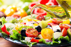 Olive oil pouring into plate of greek salad Stock Photography
