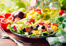Olive oil pouring into plate of greek salad royalty free stock image